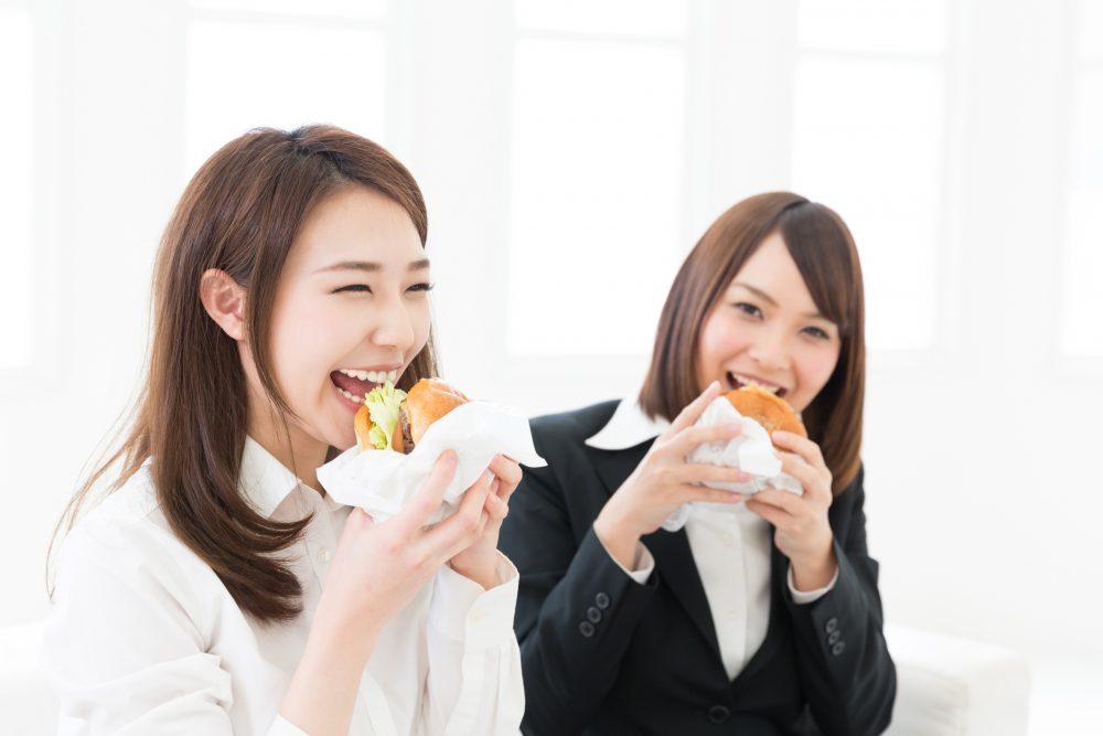ハンバーガーを食べる二人の女性